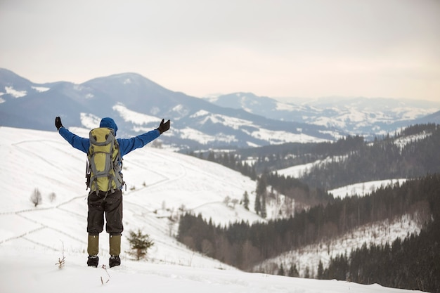 Back view of hiker in warm clothing with backpack standing with raised arms on mountain