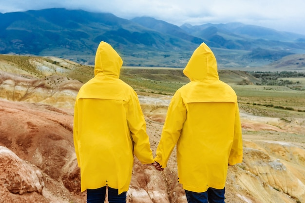 Back view hikers man and woman in yellow raincoats stand in the rain in autumn looking at the colored mountains on vacation. travel and trip concept
