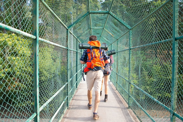 Back view of hikers walking on bridge surrounded with green grid. two tourists carrying backpacks and going through pathway. tourism, adventure and summer vacation concept