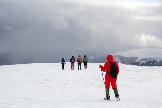 Back view of hikers walking on snow covered hill in winter mountains.
