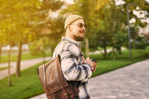 Back view of hipster bearded student looks sideways while walks in urban city park rest day