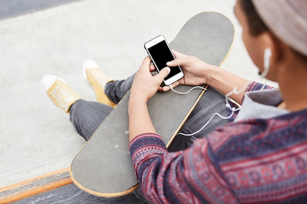 Back view of hipster teenage boy rests on skate park, skateboards with friends, holds smart phone with blank screen