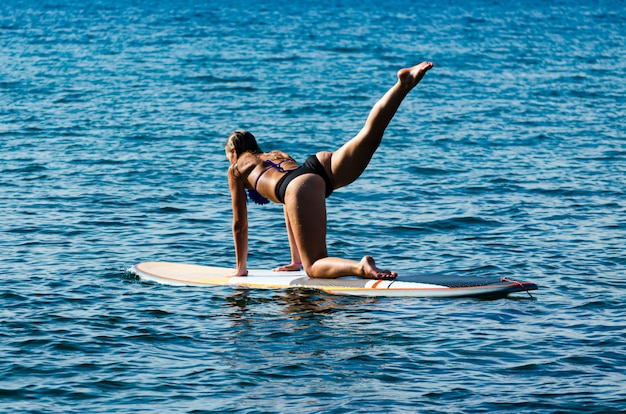 Back view of hot girl doing yoga on stand up paddle board.