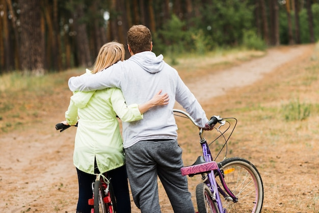 Back view hugging couple with bicycles