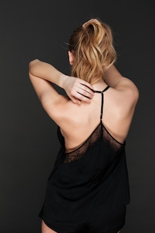 Back view image of incredible lady posing over dark wall