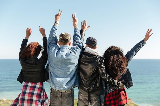 Вид сзади изображения группы друзей, стоящих на открытом воздухе