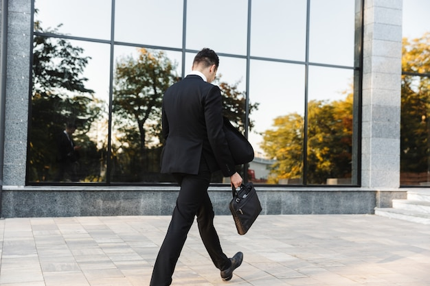 通りで屋外を歩いているハンサムな青年実業家の背面図の画像。