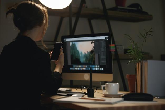 Вид сзади изображение молодой женщины дизайнер в чате по телефону.