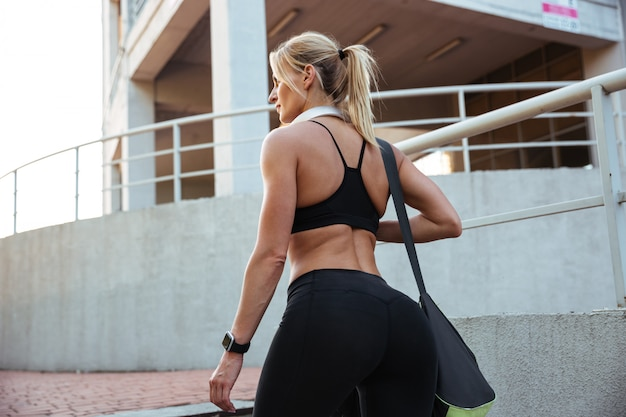 Back view image of strong young sports woman