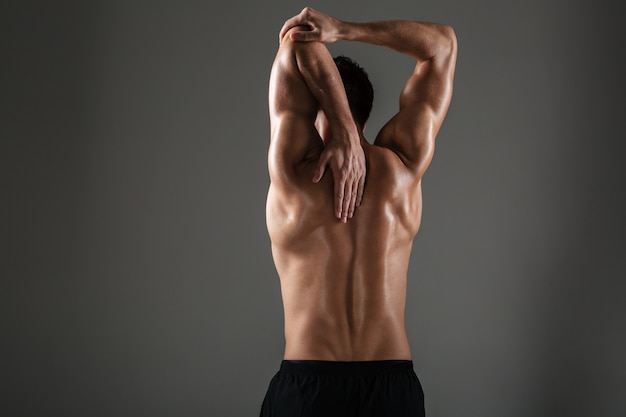 Back view image of young sports man posing