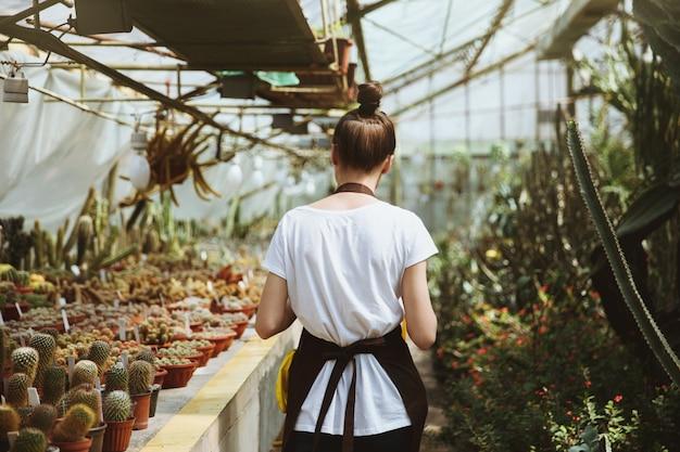Immagine di vista posteriore della giovane donna che sta nella serra