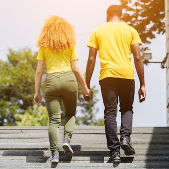 Back view of interracial couple walking upstairs