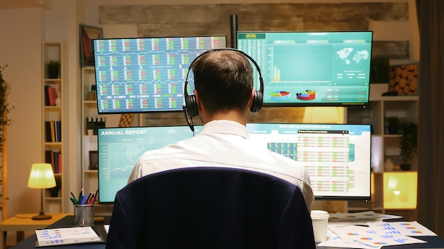 Back view of investor trading stocks online from home office. businessman with headphones.