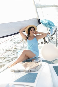 Back view of joyful attractive amazing woman in blue dress and hat enjoying azure water on the deck of a sailing yacht. concept of sailing regatta, luxury vacation at sea.