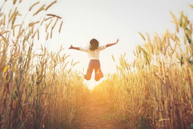 Back view of jumping girl in the barley farm