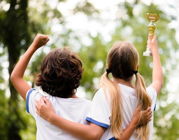 サッカーの試合に勝った後幸せな子供たちを背面します。