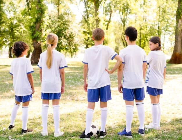 Vista posteriore dei bambini che si preparano a giocare una partita di calcio