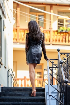 Back view of lady in short leather dress on the stairs
