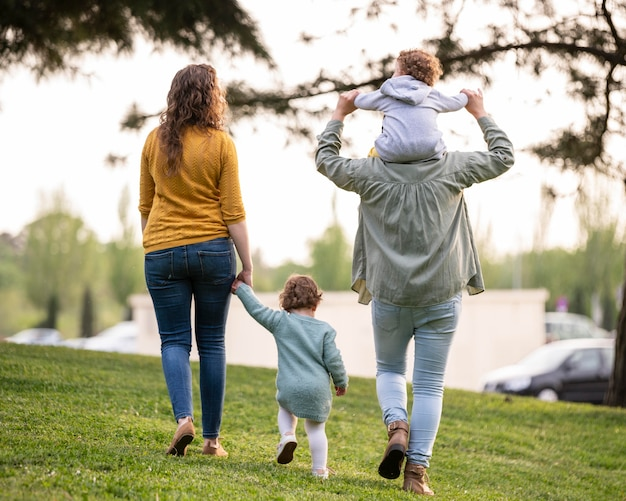Back view of lgbt mothers outside in the park with their children