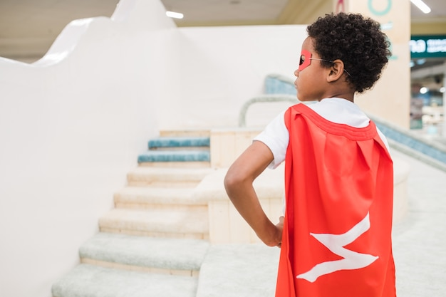 Back view of little african boy in costume of superman standing in front of camera on play area of children center