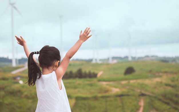 Back view of little asian child girl raise her arms looking at wind turbine field