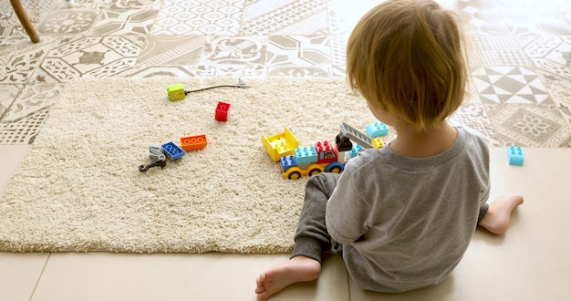 Back view of little baby sitting on floor and playing with colorful bricks