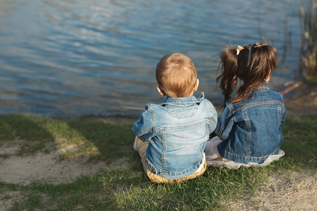 Back view of a little boy and girl sitting on the shore of a pond at sunset.