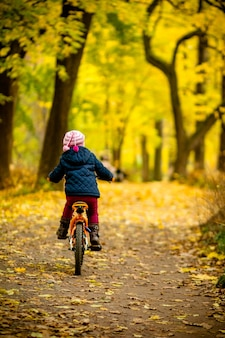 Back view of little child in blue coat riding a bicycle.