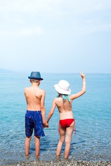 Back view of little girl and boy holding hands at the seaside.