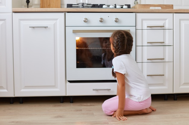 Back view of little girl sitting near oven in kitchen on the floor, having dark hair and pigtails, wearing white pigtails and rose shorts, waiting hot sweet pastry.