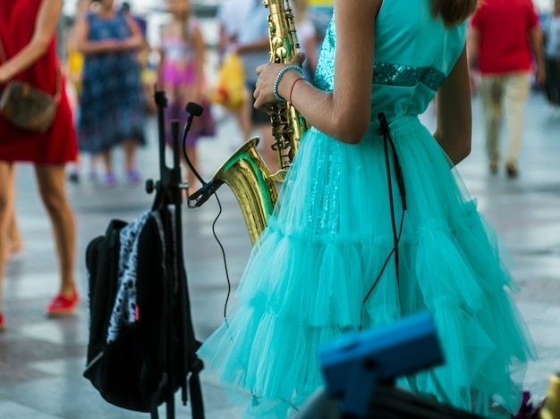Back view little girl standing in the crowded street and playing saxophone music