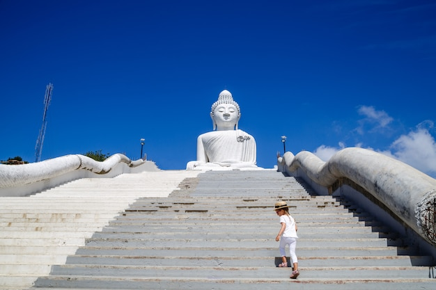 Back view of little girl standing near big buddha statue in phuket, thailand.