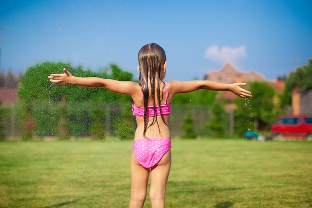 Back view of little girl in a swimsuit playing and splashing
