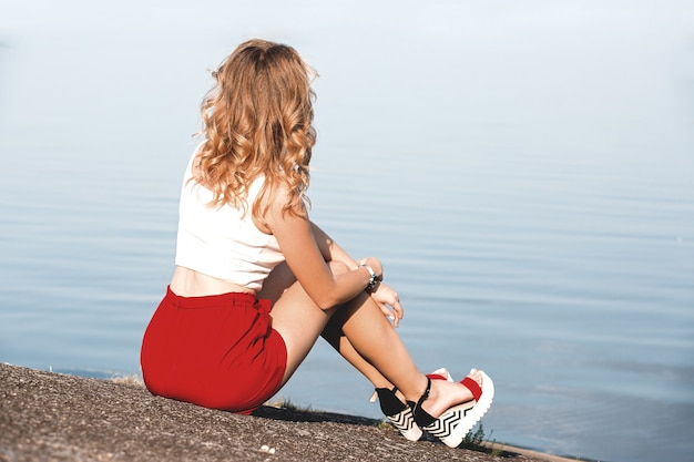 Back view of lonely caucasian girl sitting on the ground near lake at morning time. blue sea