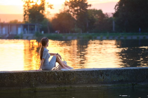 Back view of lonely woman sitting on lake shore on warm evening. solitude and relaxation concept.