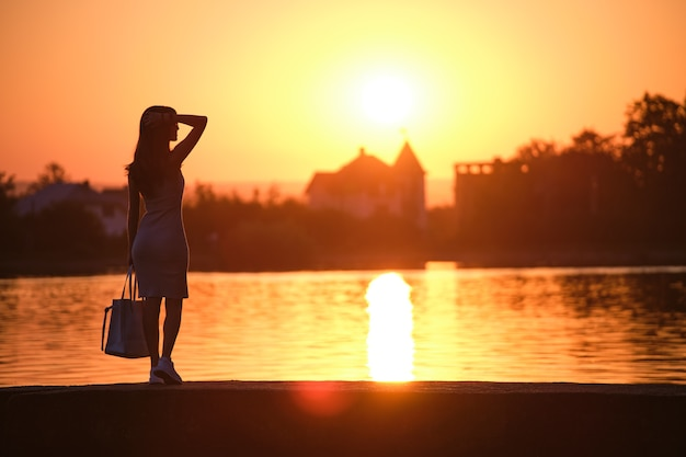 Back view of lonely woman standing on lake side on warm evening. solitude and relaxation concept.