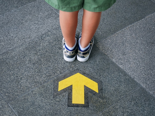 Back view of low section of kid standing in front of yellow directional arrow