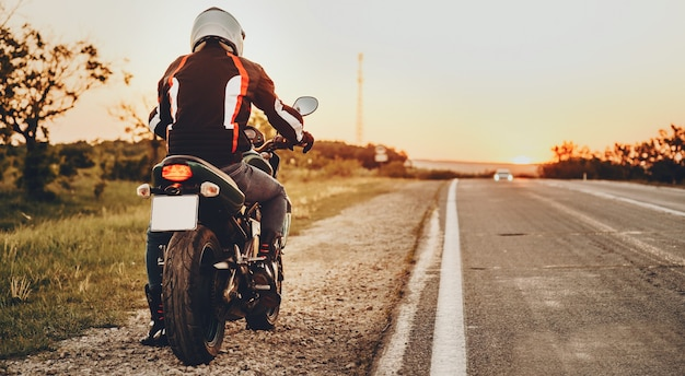 Back view of a male biker starting to go near the road in his trip on the bike .