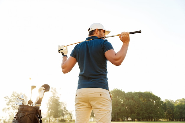Back view of a male golf player at the course with a club sack