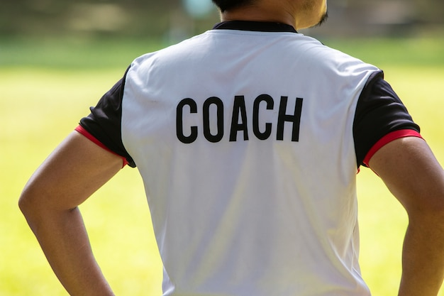Back view of male soccer or football coach in white shirt with word coach written on back