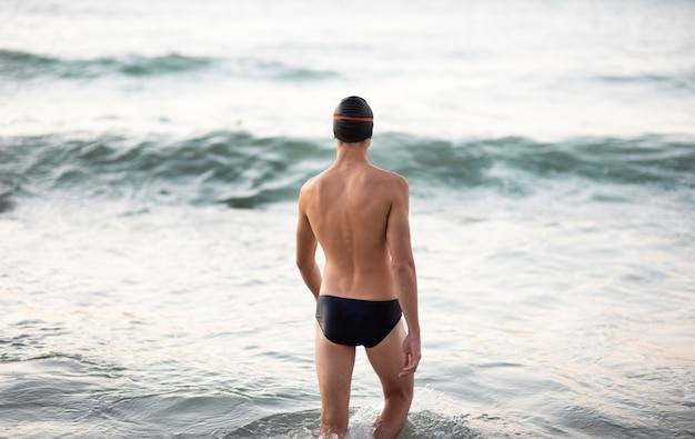 Back view of male swimmer getting in the ocean
