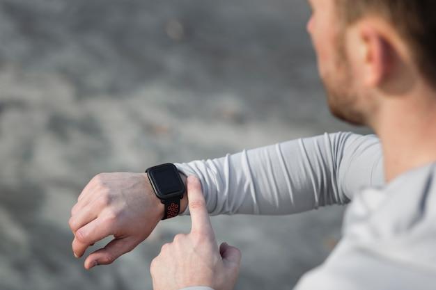 彼のスポーツの腕時計を調整する背面図男