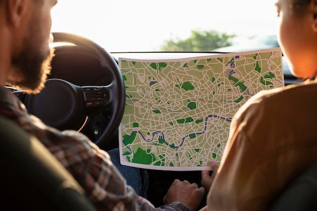 地図をチェックする男性と女性の背面図
