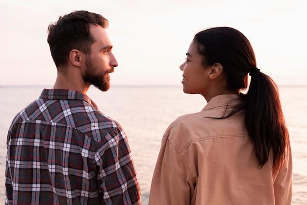 お互いを見ている背面図の男性と女性
