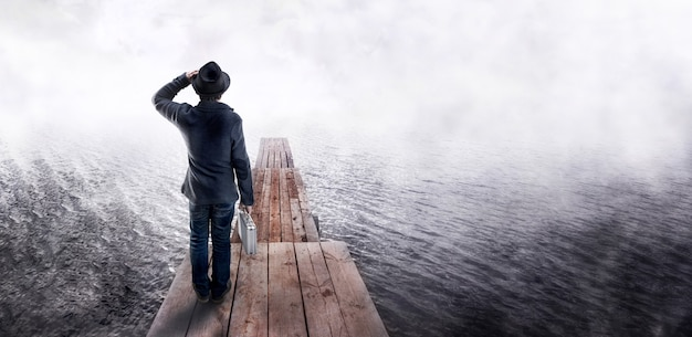 Back view of a man in black hat, holding business case, standing on wooden pier and looking into the distance. waiting and looking for business idea concept.