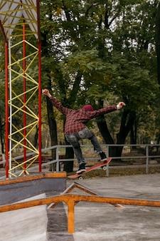 Vista posteriore dell'uomo che fa i trucchi con lo skateboard all'aperto nel parco