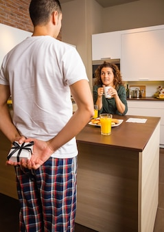 Back view of man hiding a gift box behind his back and his surprised girlfriend waiting while having breakfast on the home kitchen