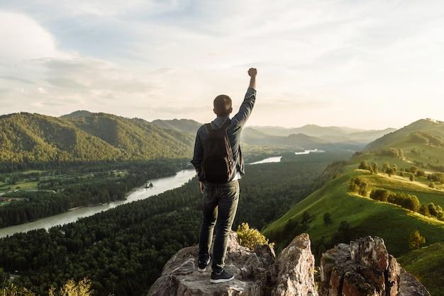 다시보기 산 꼭대기에 우승자의 포즈에 제기 손으로 배낭 남자 등산객. 산에서의 여행과 휴가의 개념