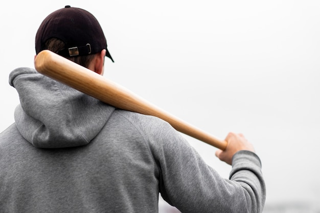 Back view of man holding baseball bat on shoulder
