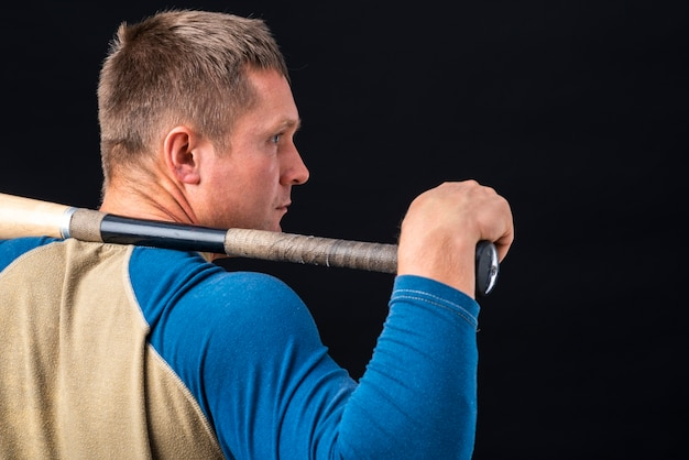Back view of man holding baseball bat